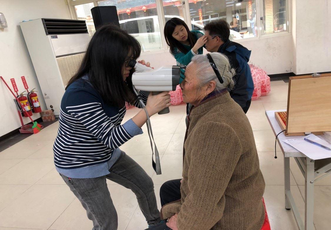 愛盲老師使用手持式驗光機為民眾測量 的圖片