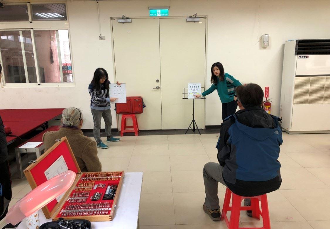 愛盲老師為民眾測量視力及辨別數字大小 的圖片
